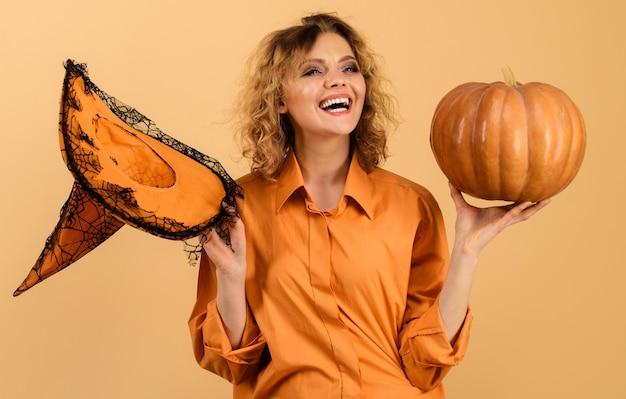 Wesołego halloween. uśmiechnięta kobieta z kapeluszem czarownicy i banią. 31 października.