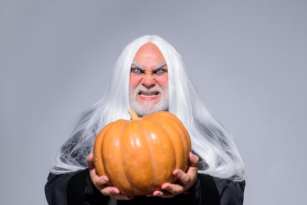 Wesołego halloween zły czarodziej trzyma człowieka z dyni w kapeluszu wiedźmy tradycyjne jedzenie fantasy horror halloween