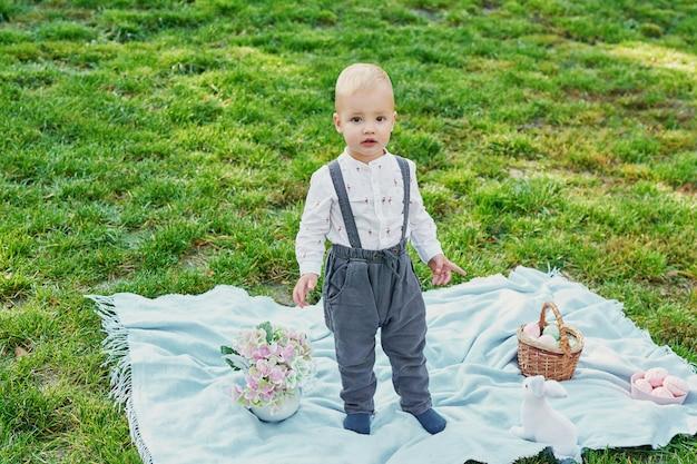 Wesołego króliczka wielkanocnego. zabawy na świeżym powietrzu. żartuje bawić się z jajkami i królikiem na zielonej trawie.
