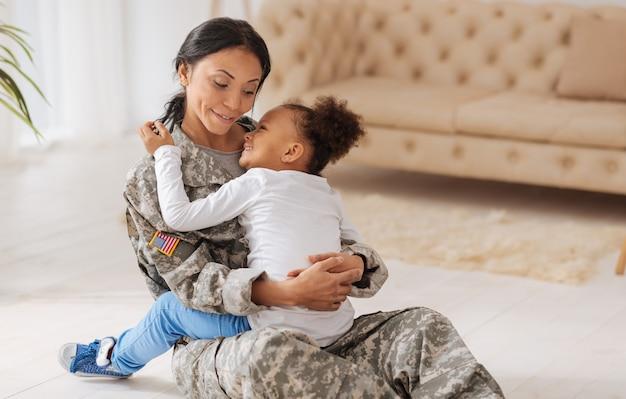 Wesołego spotkania. piękna odważna młoda kobieta siedzi na podłodze i trzyma córkę w ramionach po tym, jak nie widziała jej przez jakiś czas