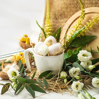 Wesołego stołu wielkanocnego. pisanka w gnieździe z kwiatową dekoracją w pobliżu okna. jaja przepiórcze. wesołych świąt wielkanocnych