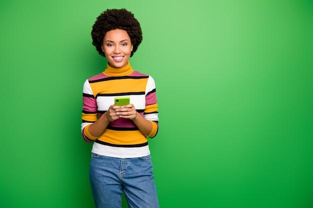 Wesołej blogerki o ciemnej skórze falistej pani trzymającej telefon za ręce osoba uzależniona od nowoczesnej technologii nosi casualowe dżinsy w paski