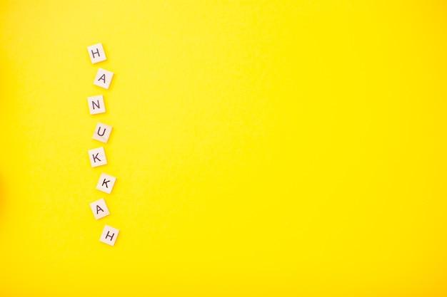 Wesołej chanuki drewniane klocki napis na jasnożółtym kolorze