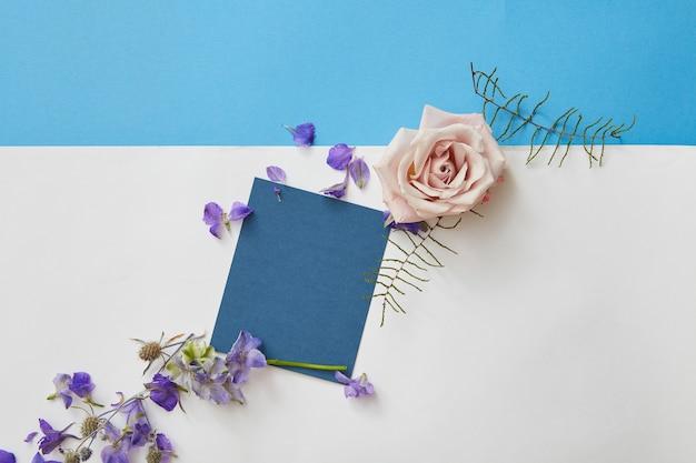 Wesołej wiosny napis. powitanie niebieska karta z pustą przestrzenią i kwiatami wokół. widok z góry, układ płaski