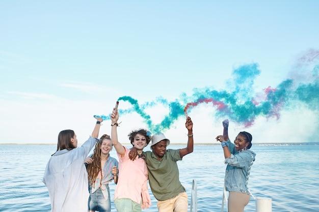 Wesoli międzykulturowi młodzi przyjaciele tańczą nad wodą