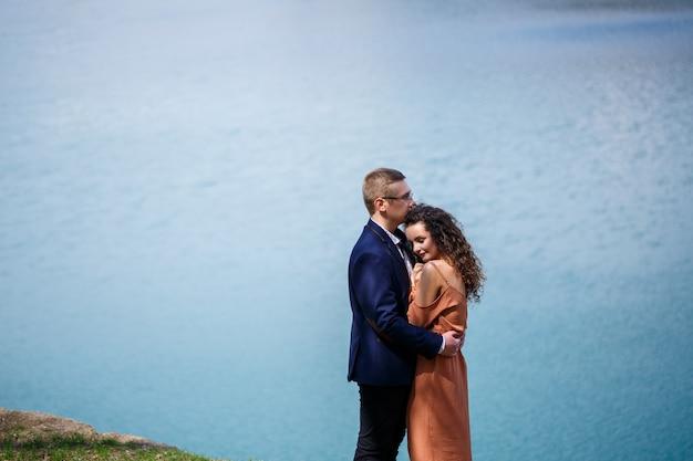 Wesoli nowożeńcy idą trzymając się za ręce i śmiejąc się, na tle jeziora i zielonej łąki. wesoły pan młody i piękna panna młoda z kręconymi włosami spacerują po łące