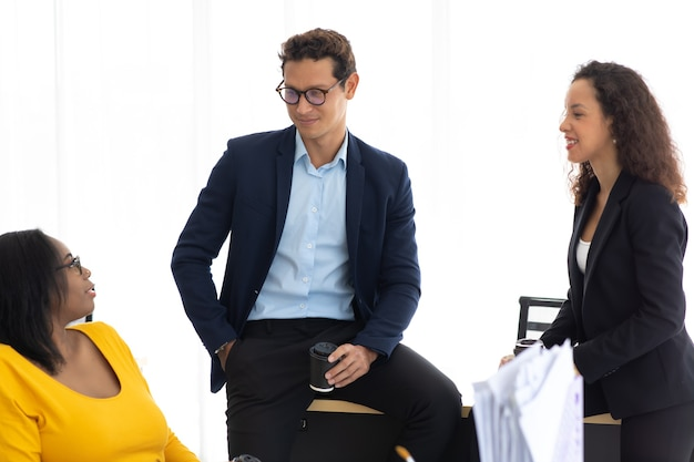 Wesoli pracownicy biurowi firmy omawiają burzę mózgów podczas wspólnego spotkania
