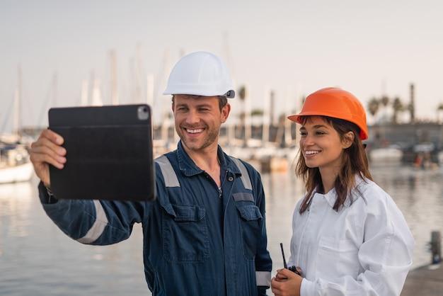 Wesoli pracownicy portu z tabletem