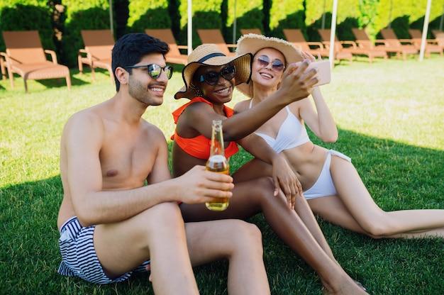 Wesoli przyjaciele piją razem piwo przy basenie. szczęśliwi ludzie bawią się na letnich wakacjach, wakacyjna impreza przy basenie na świeżym powietrzu opalając się