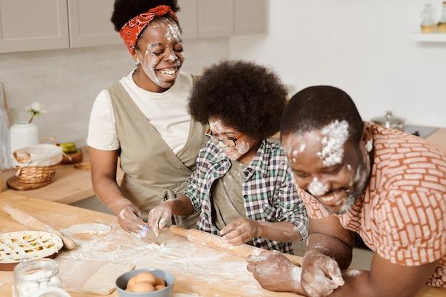Wesoli rodzice i ich synek bawią się przy gotowaniu ciasta