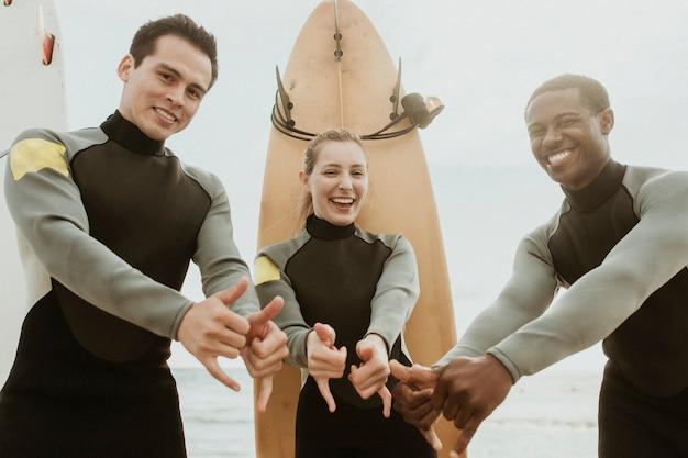 Wesoli surferzy robiący znak shaka
