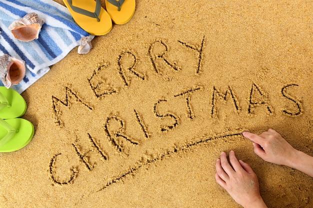 Wesoło bożych narodzeń wiadomość pisać w piasku na pogodnej plaży