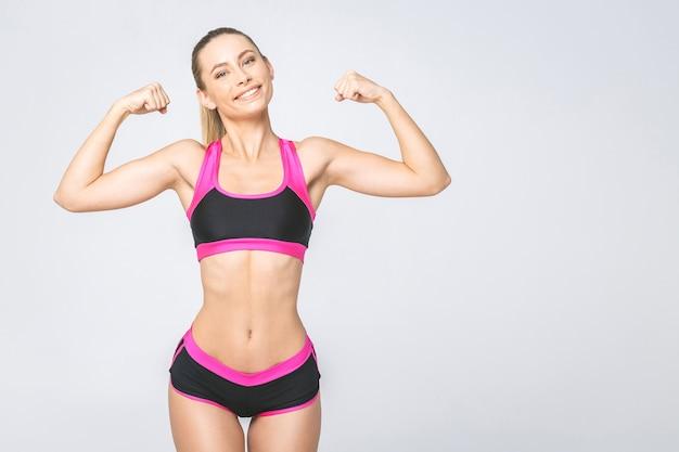 Wesoło piękna uśmiechnięta sportowa kobieta wykazująca bicepsy