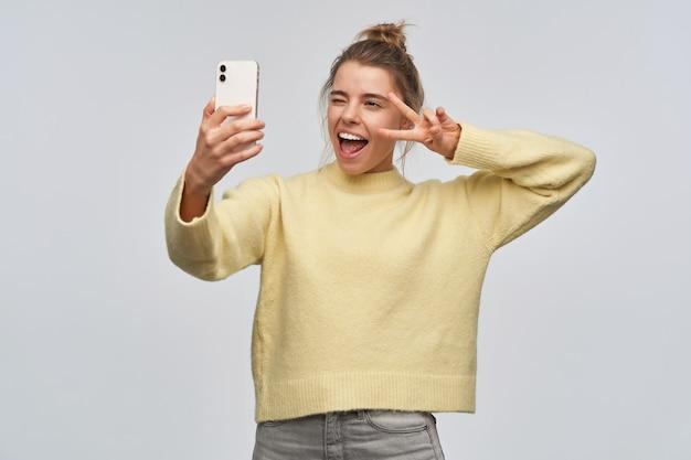 Wesoło wyglądająca kobieta o blond włosach zebranych w kok. noszenie żółtego swetra i trzymanie smartfona. robię selfie. pokazuje znak pokoju nad okiem i mruga. stań na białym tle nad białą ścianą