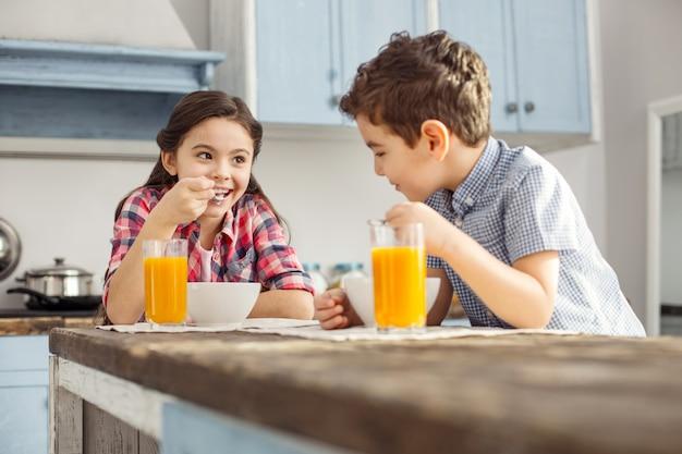 Wesołość. całkiem zainspirowana ciemnowłosa dziewczynka uśmiecha się i patrzy na swojego brata podczas śniadania