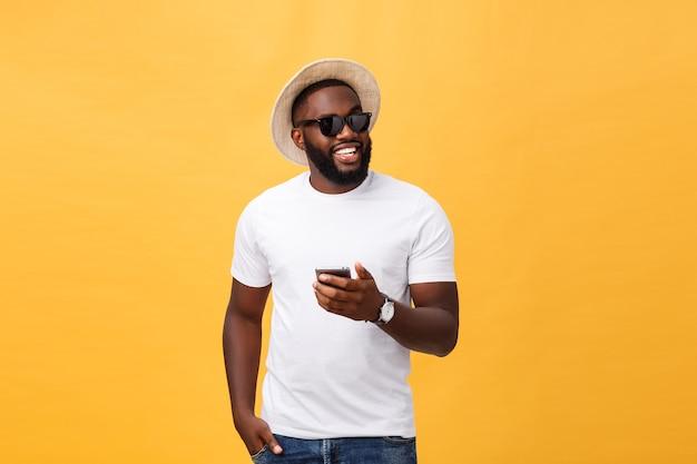 Wesoły african american człowiek w białej koszuli za pomocą aplikacji na telefon komórkowy.