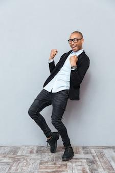 Wesoły afroamerykanin młody człowiek świętujący sukces