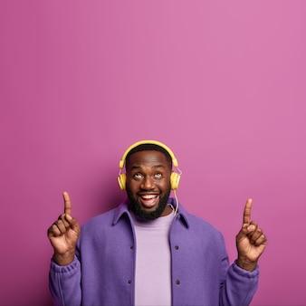 Wesoły afroamerykanin wskazuje powyżej na puste miejsce, ma dobry nastrój, słuchając żywej muzyki w słuchawkach, czuje się optymistycznie i szczęśliwie