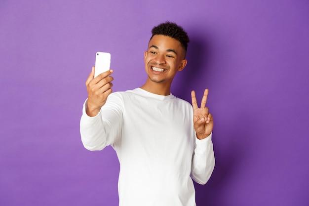 Wesoły afroamerykański bloger robi selfie na smartfonie pokazując znak pokoju i uśmiechając się do ...