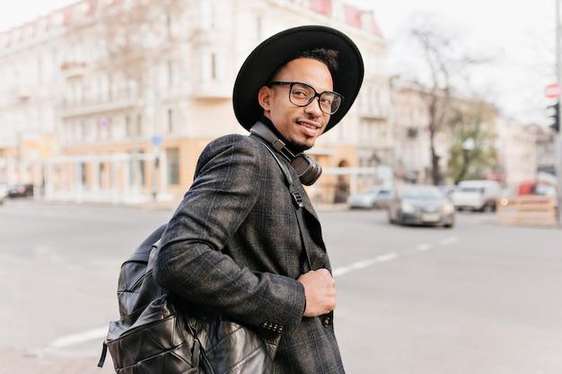 Wesoły afrykański mężczyzna ze skórzanym plecakiem, pozowanie na ulicy. plenerowe zdjęcie mulata nosi stylowe dodatki, patrząc przez ramię.
