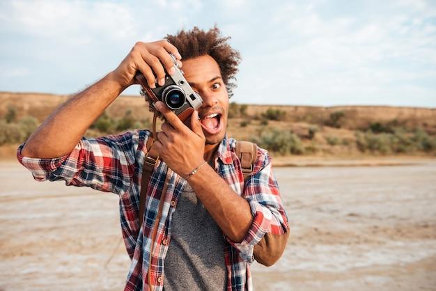 Wesoły afrykański młody człowiek robi zdjęcia i bawi się na plaży