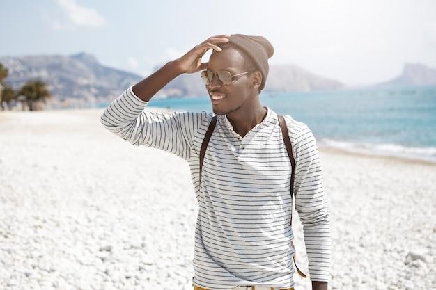 Wesoły afrykański młody człowiek stojący na plaży i patrząc na bok z rozkosznym uśmiechem zauważył zbliżającego się przyjaciela dotykającego głowy. letnie wakacje i przygody. ludzie, styl życia i podróże