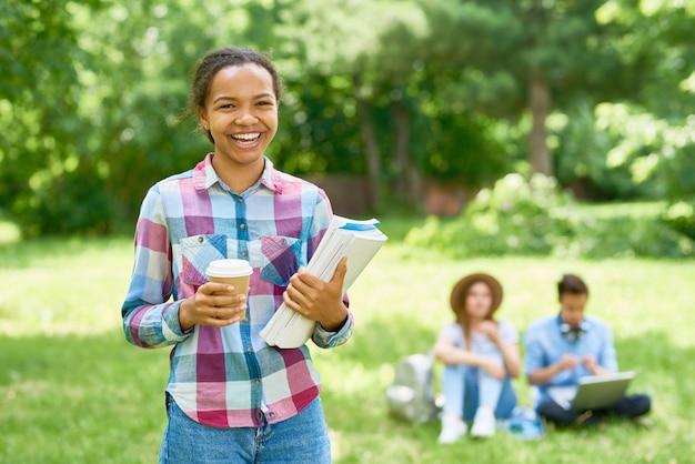 Wesoły afrykański student na trawniku kampusu