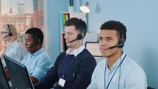 Wesoły agent obsługi klienta o mieszanym pochodzeniu etnicznym rozmawia przez telefon z zestawem słuchawkowym