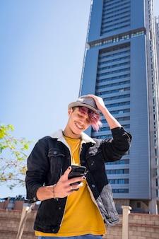 Wesoły alternatywny młody mężczyzna nastolatek używa telefonu komórkowego do pisania