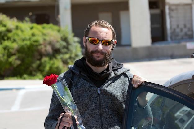 Wesoły amerykański przystojny brodaty mężczyzna nosi okulary przeciwsłoneczne i kurtkę z kapturem wysiada z samochodu w mieście. brutalny rosjanin trzymający w ręku czerwony kwiat róży. romantyczna, walentynkowa koncepcja wakacji