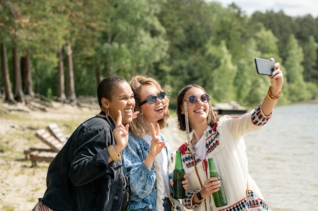 Wesoły, atrakcyjne młode wieloetniczne kobiety z butelkami piwa, razem biorąc selfie na plaży