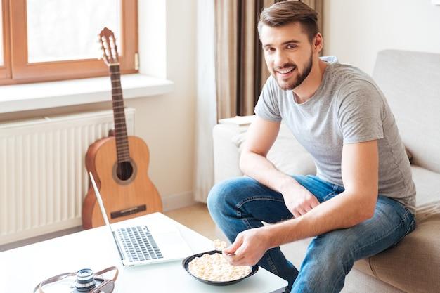 Wesoły, atrakcyjny brodaty mężczyzna z laptopem siedzący na kanapie i jedzący płatki z mlekiem