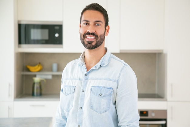 Wesoły atrakcyjny ciemnowłosy mężczyzna łaciński pozowanie w kuchni