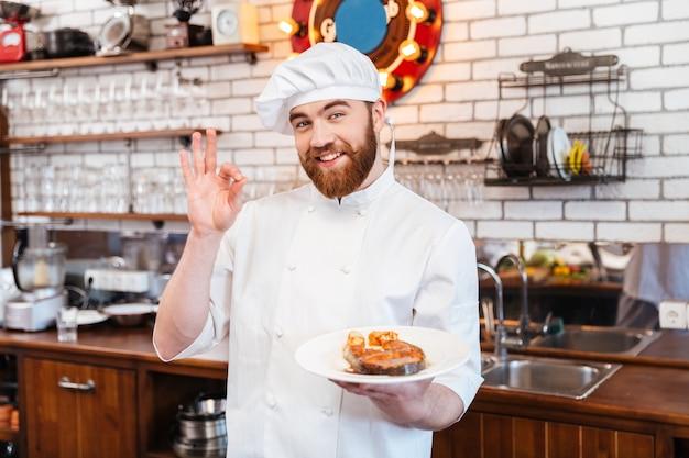 Wesoły, atrakcyjny kucharz trzyma przygotowany stek z łososia na talerzu i pokazuje ok gest w kuchni gesture
