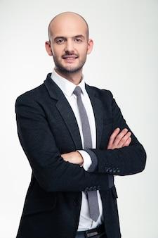 Wesoły atrakcyjny młody biznesmen stojący ze skrzyżowanymi rękami na białej ścianie