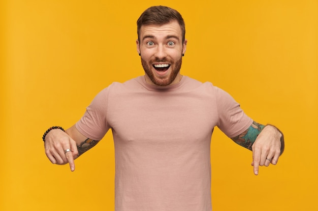 Wesoły atrakcyjny młody brodaty mężczyzna z tatuażem na dłoni w różowej koszulce wygląda na podekscytowanego i wskazuje palcami obu rąk na żółtą ścianę