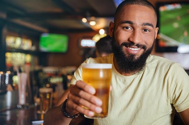 Wesoły, atrakcyjny młody człowiek pijący piwo w pubie