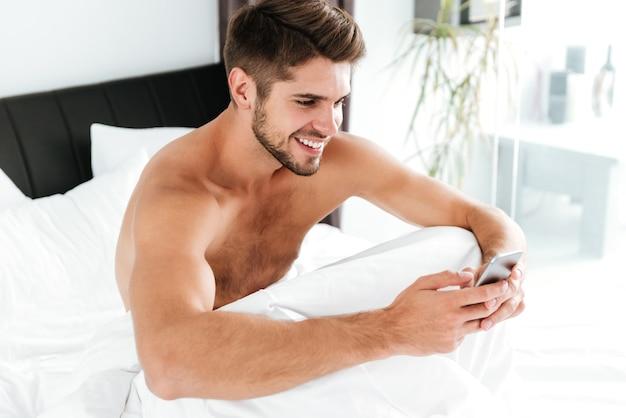Wesoły atrakcyjny młody człowiek siedzi i przy użyciu telefonu komórkowego w łóżku
