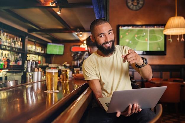 Wesoły, atrakcyjny młody mężczyzna z laptopem siedzi w pubie i wskazuje na ciebie