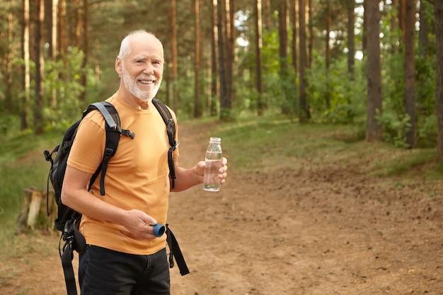 Wesoły atrakcyjny starszy mężczyzna wędruje z plecakiem na zewnątrz, uśmiecha się radośnie zaspokajając pragnienie, trzymając butelkę z wodą pitną, pozuje w sosnowym lesie. wiek, dojrzałość i aktywny tryb życia
