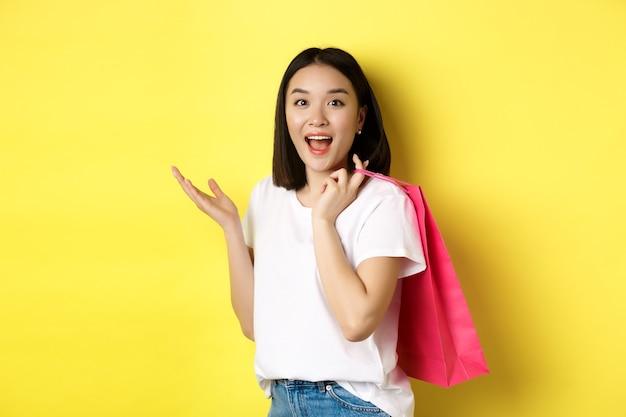 Wesoły azjatycki kupujący kobieta wygląda rozbawiony, trzymając torbę na zakupy i stojąc na żółto.