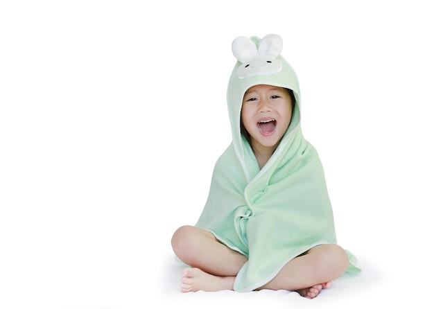Wesoły azjatyckie małe dziecko dziewczynka uśmiechnięta pokrywa ciała pod ręcznikiem po kąpieli, siedząc na łóżku na białym tle