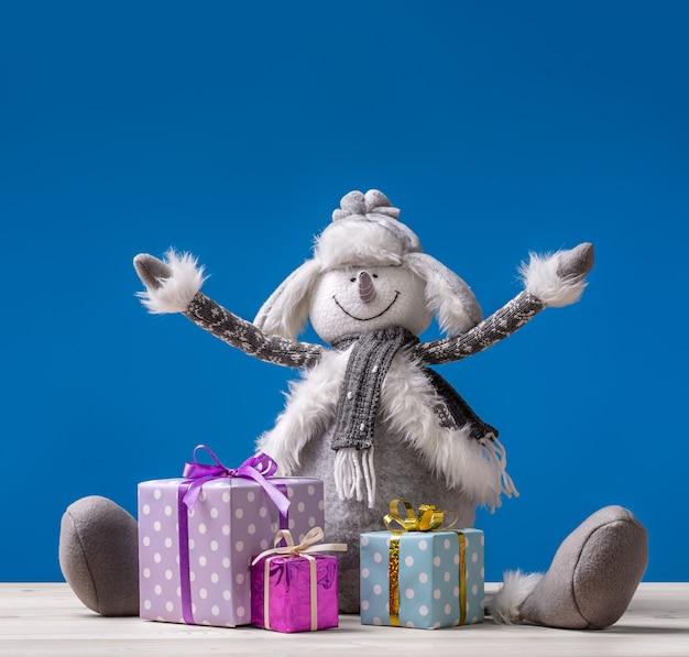 Wesoły bałwanek ze świątecznymi prezentami w pudełkach przesyła życzenia noworoczne