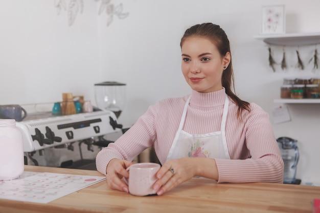 Wesoły barista serwujący kawę pracujący w lokalnej kawiarni