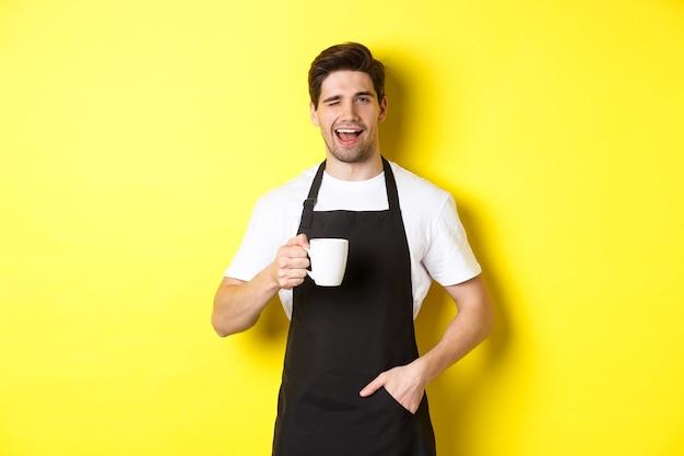 Wesoły barista w czarnym fartuchu, serwujący kawę i mrugający, stojący przy żółtej ścianie