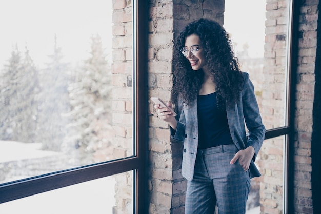 Wesoły biznes dama przegląda smartfon w pokoju w stylu loftu