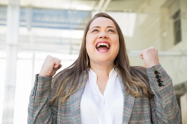 Wesoły biznes dama świętuje sukces na zewnątrz