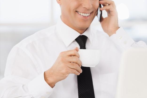 Wesoły biznesmen. przycięty obraz uśmiechniętego dojrzałego mężczyzny w formalnej odzieży pijącego kawę i rozmawiającego przez telefon komórkowy, siedząc w swoim miejscu pracy