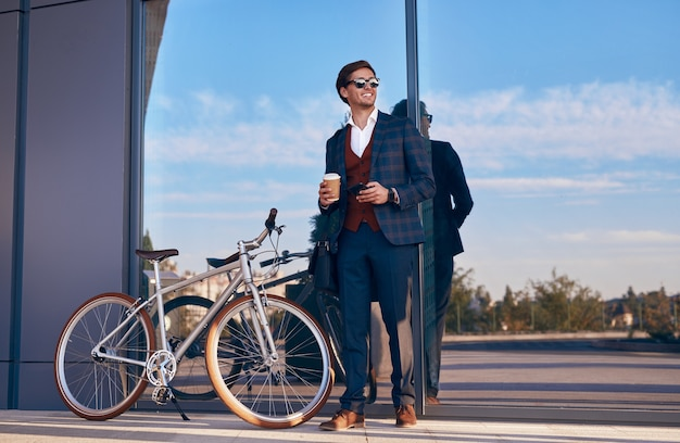 Wesoły biznesmen z rowerem i kawą na wynos
