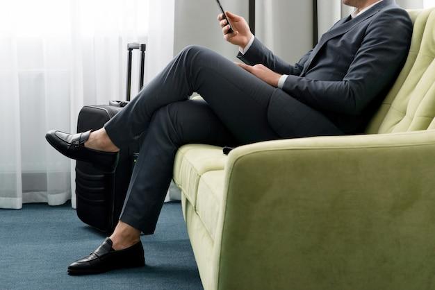Wesoły biznesmen za pomocą telefonu siedzi w pokoju hotelowym z walizką w podróży służbowej
